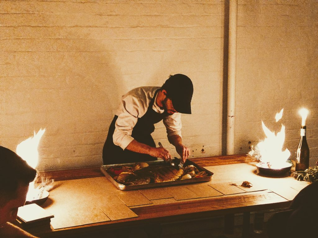 A chef preparing a large pan of food with flaming pans on either side of him