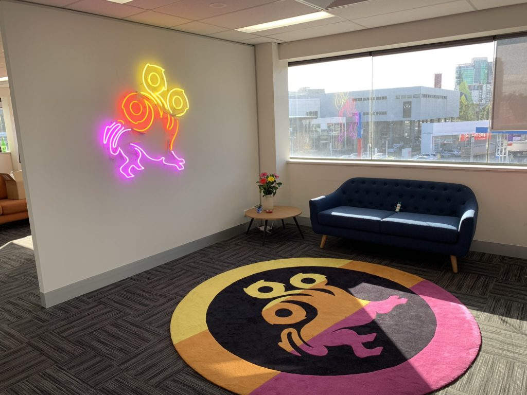 A wall with a neon sign version of the League of Geeks logo on it and a rug with the League of Geeks logo on it in front