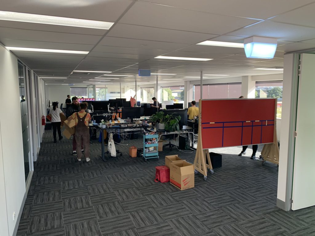 An office scene featuring people carrying items, desks, and boards