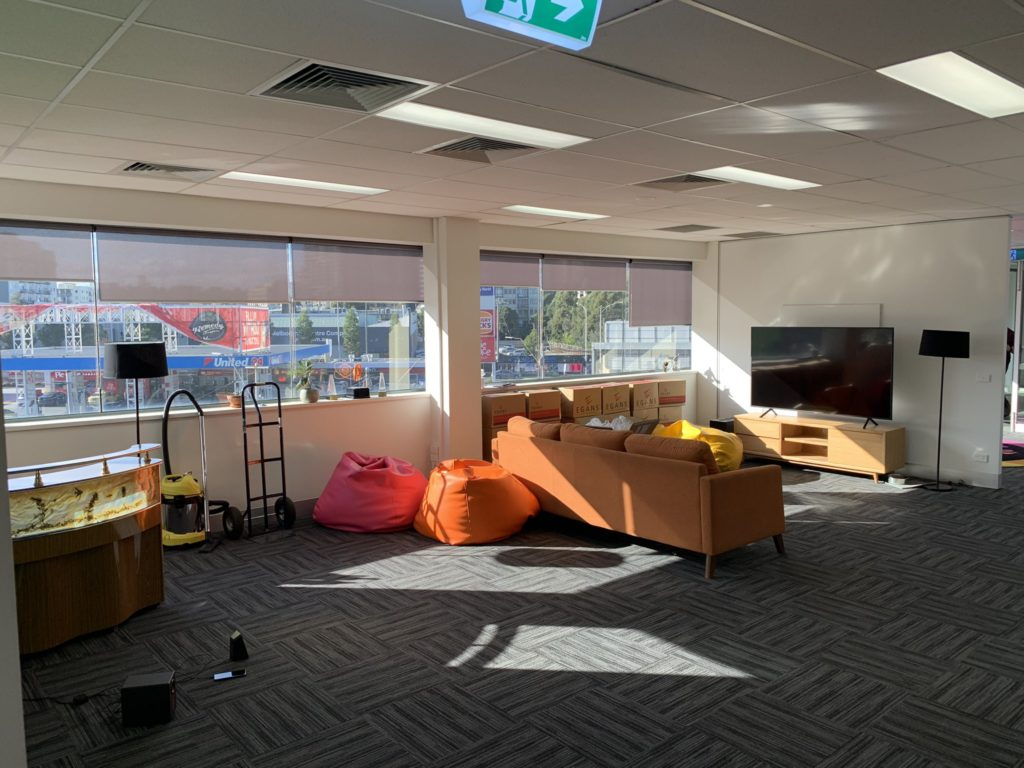 An empty breakout area of an office with a large TV and sofa