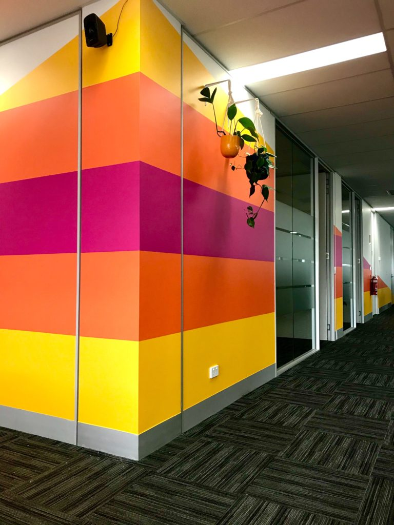 An office hallway featuring bright yellow, orange, and pink striped walls
